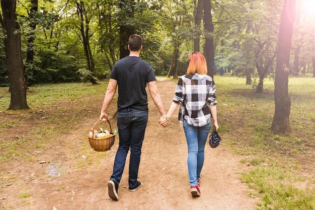 公園でのダートロードを歩くピクニックバスケットを持っているカップルのリアビュー 無料写真