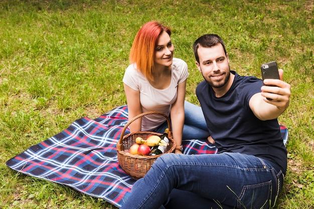 ピクニックで携帯電話で彼女の笑顔のガールフレンドとセルフを取る男 無料写真