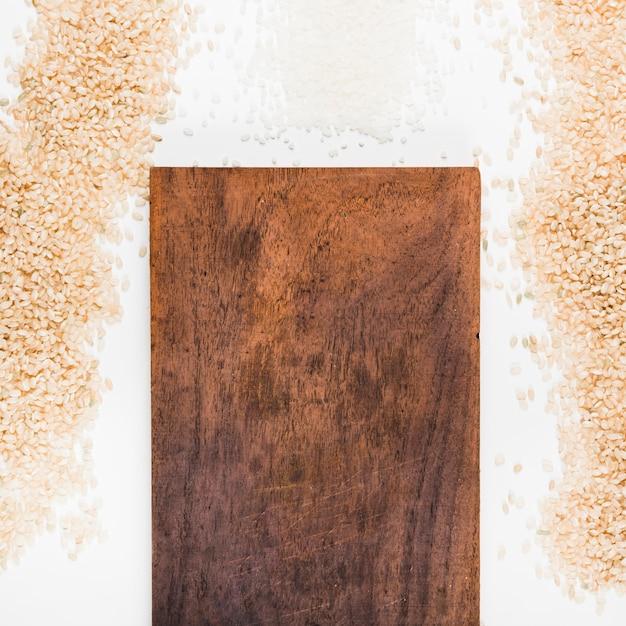 木製のチョッピングボードを持つ生の米 無料写真