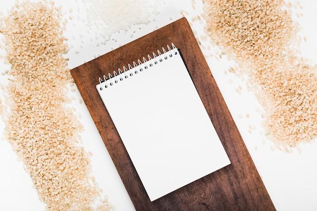 白い背景に米の様々な木製トレイにスパイラルメモ帳 無料写真