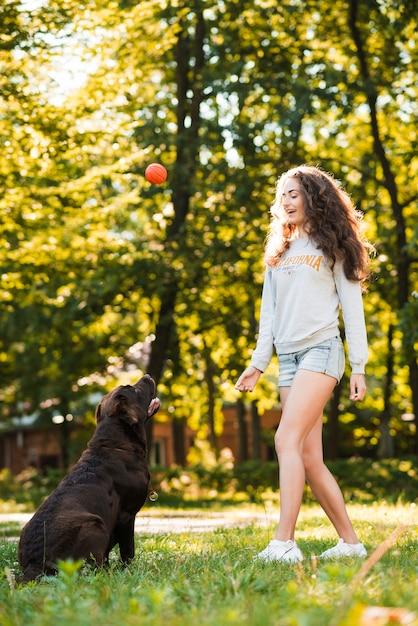 庭で彼女の犬とボールを演奏する女性 無料写真