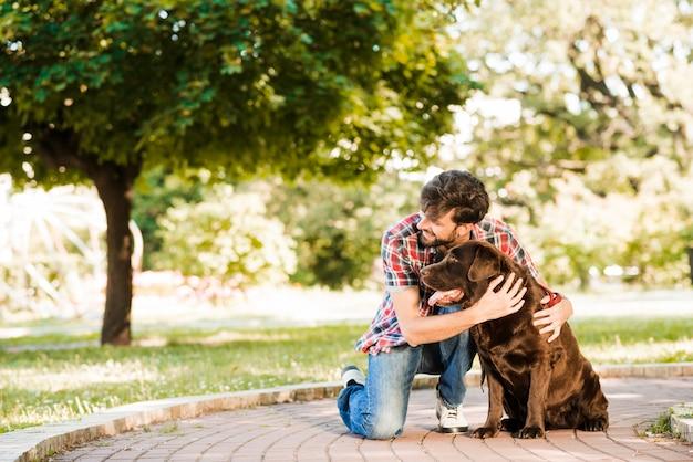 公園の歩道に彼の犬を持つ男 無料写真