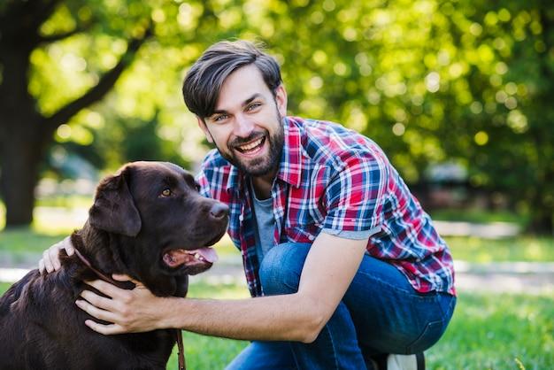 公園で彼の犬と幸せな若い男の肖像画 無料写真
