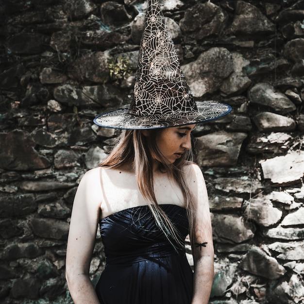 Молодая женщина в платье и шляпа ведьма, глядя в сторону Бесплатные Фотографии