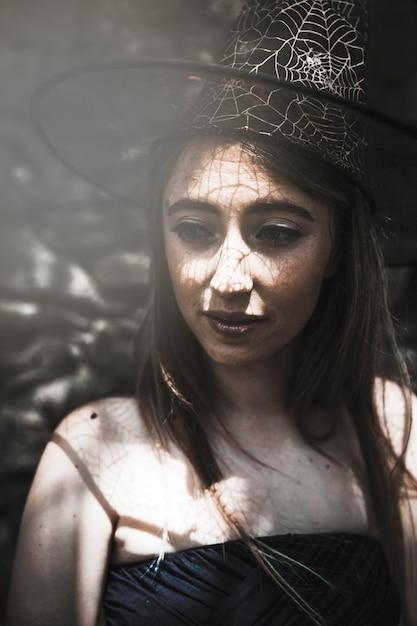 Молодая женщина в шляпе ведьм, глядя в сторону Бесплатные Фотографии