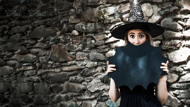 Молодая женщина в шляпе ведьмы, закрывающей рот с украшением хэллоуина Бесплатные Фотографии