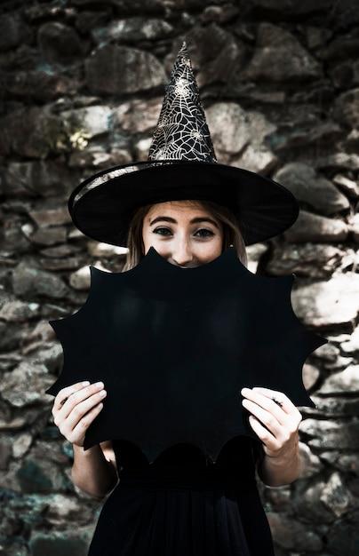 Молодая женщина в шляпе мастера закрыть рот с хэллоуин украшения Бесплатные Фотографии