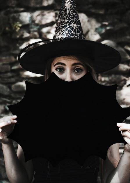 Молодая женщина в шляпе ведьмы с хэллоуин украшения, глядя на камеру Бесплатные Фотографии