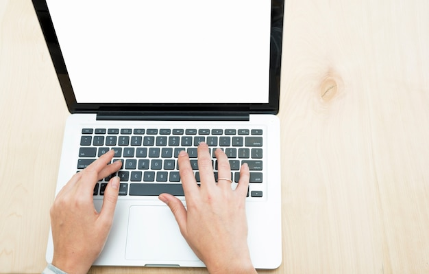 木製の背景の上にノートパソコンで入力している人の手の上の眺め 無料写真