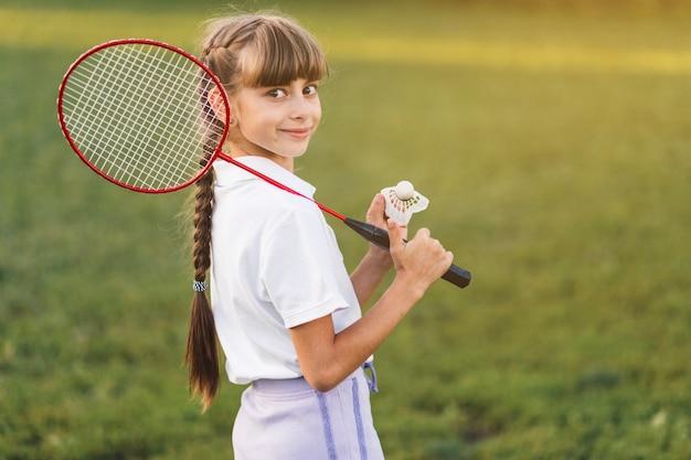 彼女の肩とシャトルコックの上にバドミントンを持っている笑顔の女の子 無料写真
