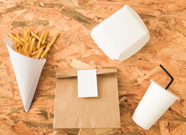 ペーパーコーンでのフライドポテトと木製の背景でのパッケージモックアップ 無料写真