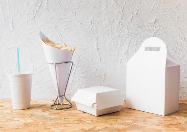 木製の表面に処分用カップと食品小包を入れたフライドポテト 無料写真