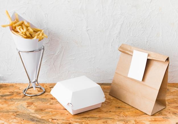 フライドポテトと食べ物のパーセルを木製のテーブルの上にモックアップ 無料写真