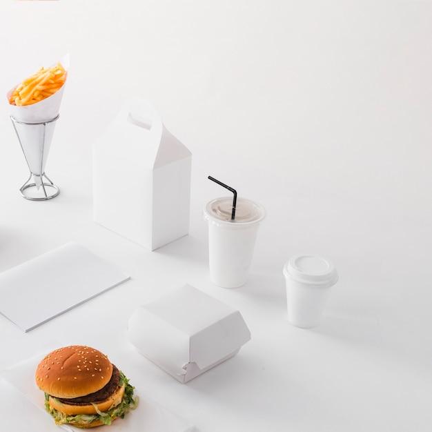 バーガー;処分用カップ;白い背景にフライドポテトと食品小包 無料写真