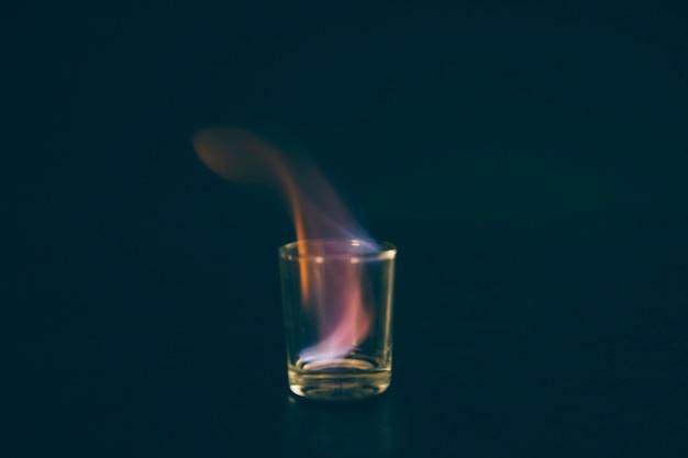 燃えるテキーラは、黒の背景にガラスを投げた 無料写真
