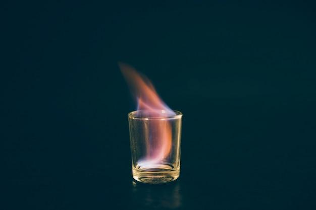 テキーラショットの黒い背景にガラスを燃やす 無料写真