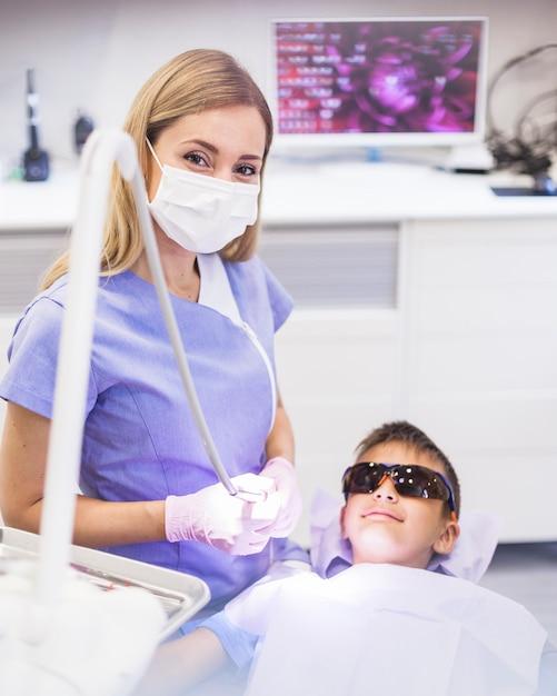 安全な保護眼鏡を着て男の子の近くに立つ女性の歯科医 無料写真