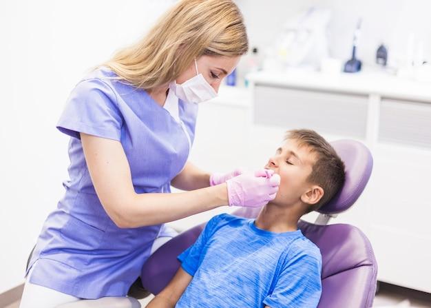 歯医者、診察中の男の子の歯を診察する 無料写真