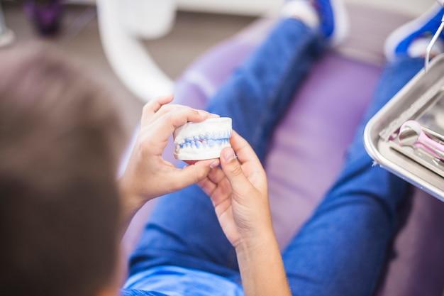 歯の石膏型を保持している男の子の手のクローズアップ 無料写真