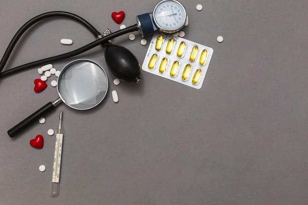 血圧計の高さ;虫眼鏡;丸薬;グレーの背景に温度計と赤い心 無料写真