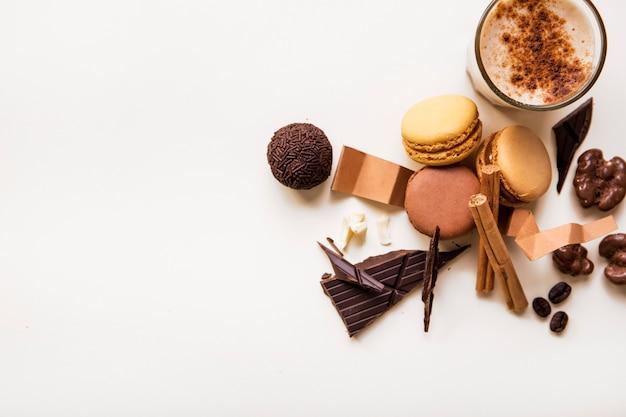マカロンのオーバーヘッドビュー。チョコレートボールと白い背景にコーヒーグラス 無料写真