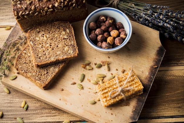 チョッピングボード上の材料とエネルギーバーを使った新鮮な有機パンの眺め 無料写真