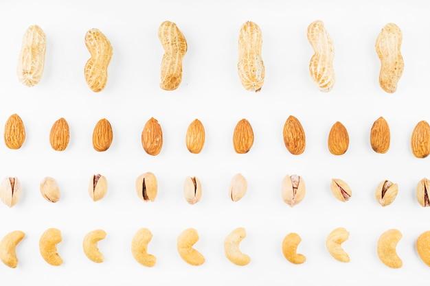 行のクルミ;ピーナッツ;アーモンド;ピスタチオ、カシューナッツ、白、背景 無料写真
