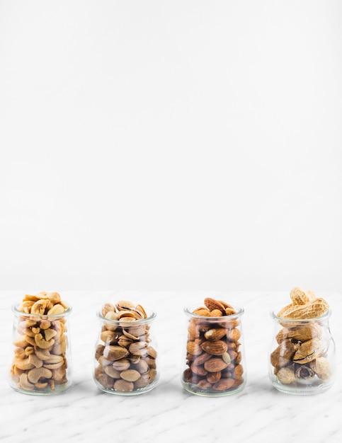 大理石の背景に新鮮なナツ食品瓶の行 無料写真