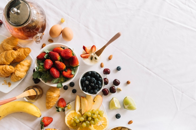 新鮮な果物の高台;ヨーグルト;白い背景に卵とクロワッサン 無料写真