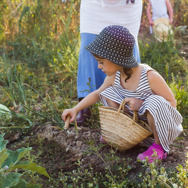 トローリングで土を掘るバスケットを持っている少女 無料写真