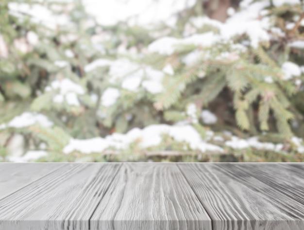 雪のクリスマスツリーの前に空の木製のテーブル 無料写真