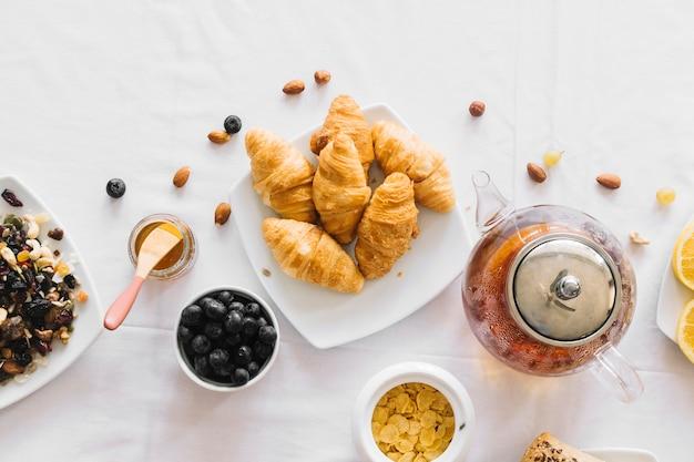 焼きたてのクロワッサンの俯瞰図。果物;白いテーブルクロスでお茶とドライフルーツ 無料写真