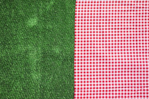 赤いチェッカーのテーブルクロスと緑の芝の背景 無料写真