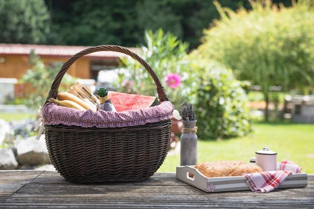 ピクニックバスケットと庭の木製テーブルのパン 無料写真