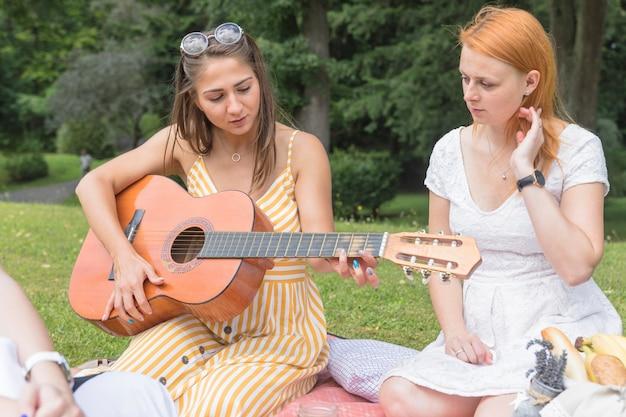 ギターを弾く女性を見ている友人 無料写真