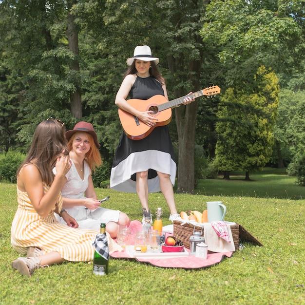 ピクニックで音楽と食べ物を楽しむ女性の友人のグループ 無料写真