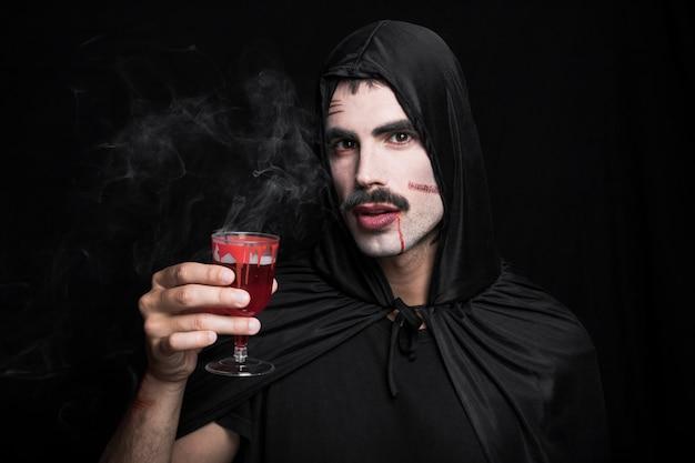 Молодой человек с царапинами на белом лицо с дымящимся напитком Бесплатные Фотографии