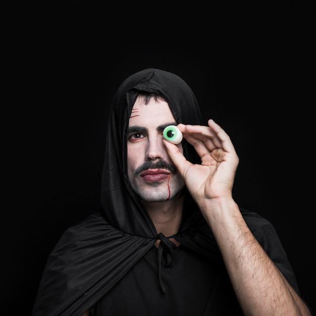 Молодой человек в черном плаще с капюшоном с искусственным глазом Бесплатные Фотографии