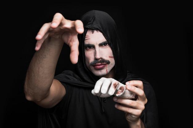 Молодой человек в черной одежде, ставит в студии с трупом руку Бесплатные Фотографии