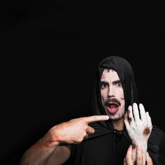 Молодой человек в черном плаще хэллоуина, указывая на руку трупа Бесплатные Фотографии