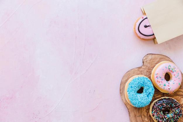 ピンクの背景の上にパッケージの近くにチョッピングボード上の新鮮なドーナツ 無料写真