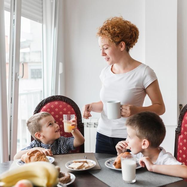 健康的な朝食をしている彼女の子供の近くに立つ女性 無料写真