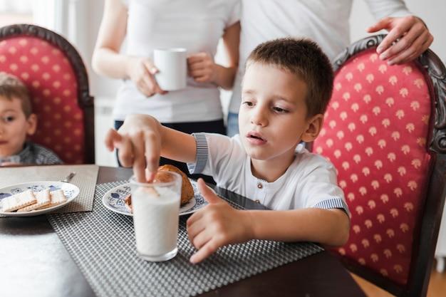 ミルクのガラスにビスケットを浸している男の子 無料写真