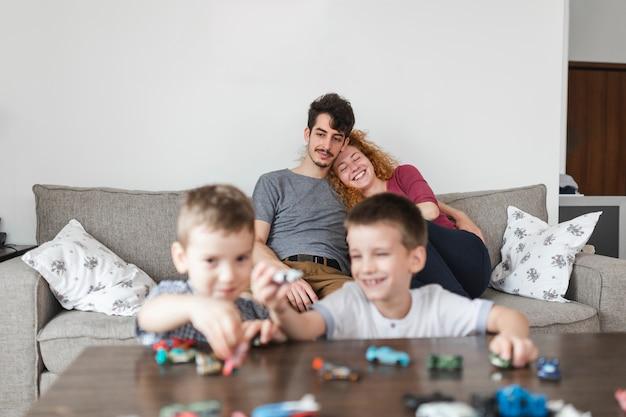 ソファに座っている両親の前で車のおもちゃで遊んでいる兄弟 無料写真