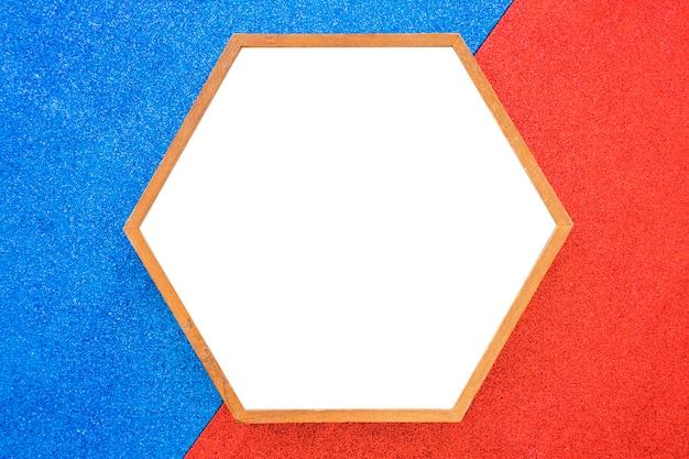 赤と青の背景に空の木製の六角形のフレーム 無料写真