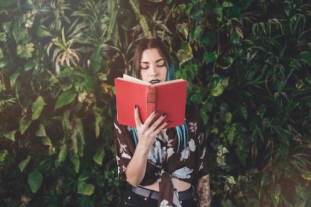 成長している植物の前に立っている現代の若い女性読書本 無料写真