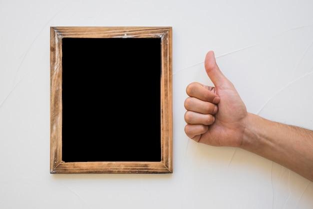 黒板の近くにサインを表示する手 無料写真