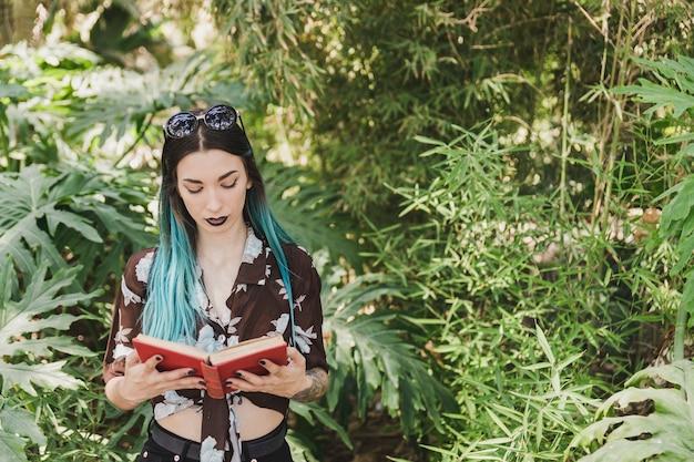 成長している植物の本の前に立っている若い女性 無料写真