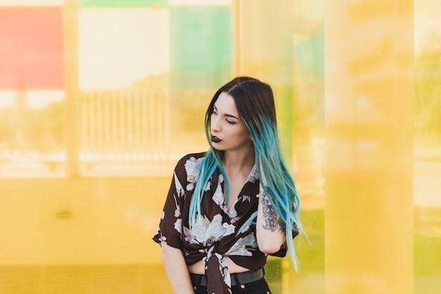 黄色の背景の前に立っている染め毛を持つ現代の若い女性 無料写真