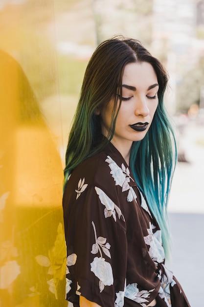 黄色の反射の背景の前に立っている染め毛のある若い女性のクローズアップ 無料写真